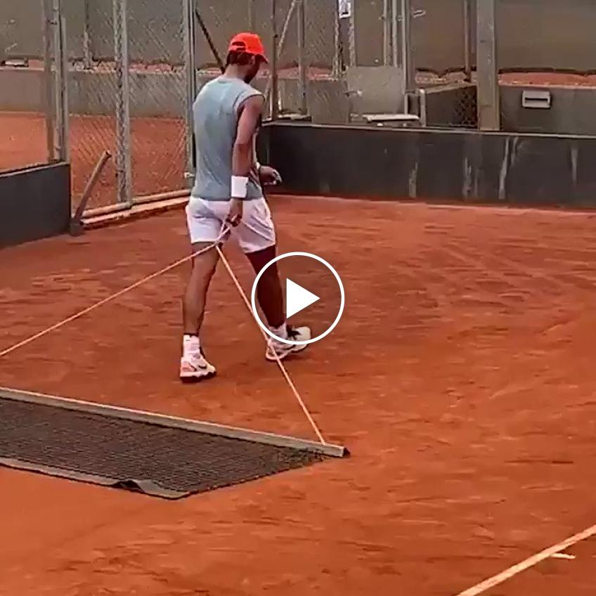 Rafael Nadal sweeps the courts after his practice session